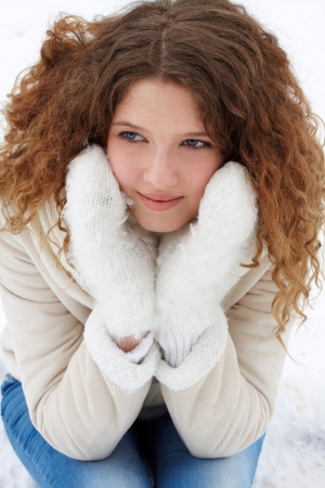 The long-haired girl in light winter clothes and blue jeans, smiling, thoughtfully looks aside Stock Photo