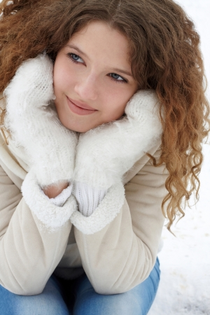 The young girl with a flowing hair in a light sheepskin coat, jeans and mittens, smiling, thoughtfully looks aside