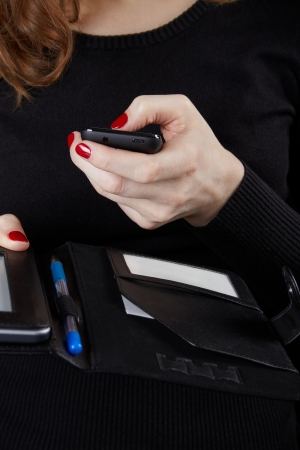 The woman in a black sweater holds the mobile phone and the tablet computer Stock Photo