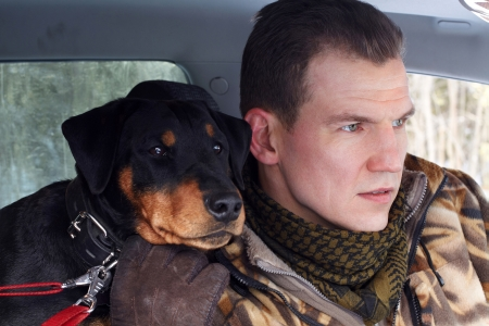 The man (Popov Dmitry) with the German hunting terrier sit in the machine.