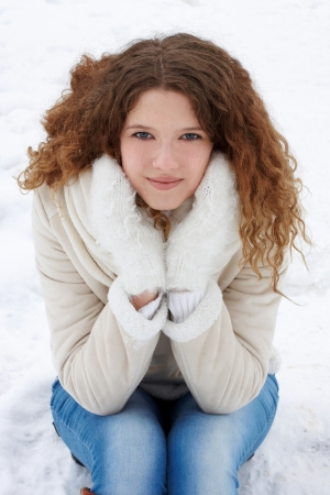 The long-haired girl in jeans and a sheepskin coat looks in the camera, listening to music Stock Photo
