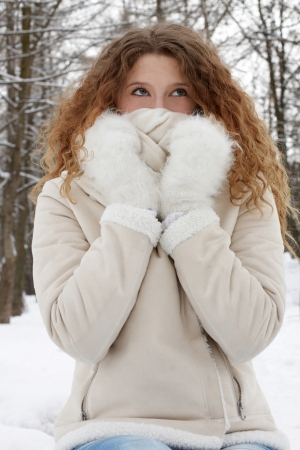 The long-haired girl in the wood looks up, muffling up in a scarf Stock Photo