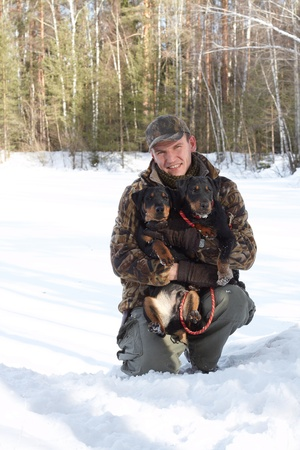 The man (Popov Dmitry) holds on hands of two hunting dogs Jagdterriers in the winter, looks in the camera Stock Photo