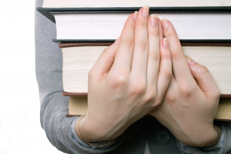 The girl holds a heavy pile of books on hands Stock Photo