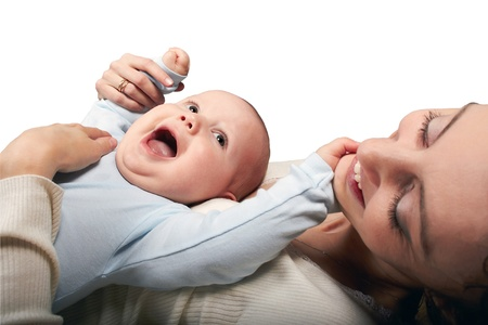 The dark-haired woman in a white jacket lies on a spin and holds on a stomach of the laughing baby. White background.