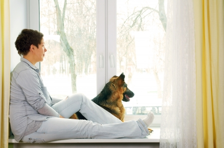 The girl with a short hairstyle in jeans clothes waits for someone sitting on a window sill and stroking a dog. Stock Photo