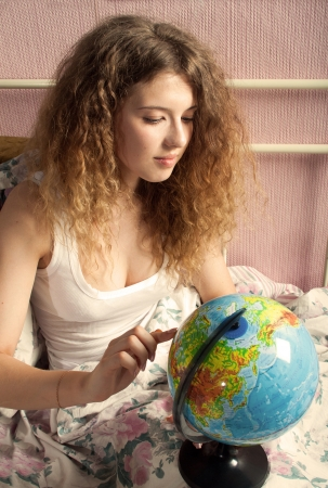 The girl with long hair and in a white undershirt looks for something on the globe in the morning, sitting on a bed.