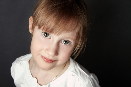 The green-eyed girl with freckles trustfully looks in the camera,black background