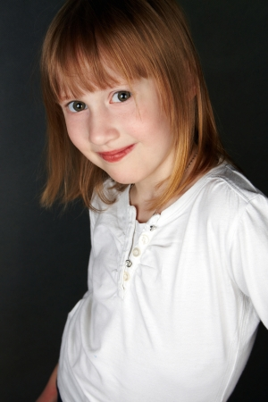 The girl with freckles and a fair hair, slightly smiling, looks in the camera. Black background