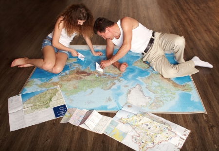 The man and the girl, for something searching, play paper ships on the map outspread on a floor Stock Photo