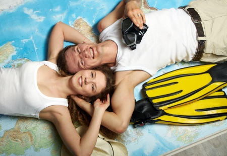 The married couple lies on a spin on the map outspread on a floor Stock Photo