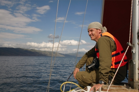 The smiling man in a life jacket sits on a nose of the yacht floating on the Lake Sevan Armenia Stock Photo