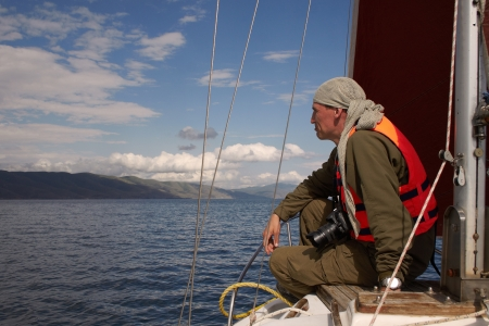 The man sits on a nose of the yacht floating on the Lake Sevan in Armenia