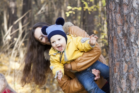 The laughing child on hands at mother who is jumping out because of a tree in the autumn wood