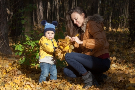 The boy in a yellow jacket collects with mother leaves on a forest glade