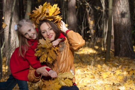 The girl in a red coat and a bouquet of leaves embraces mother against the wood