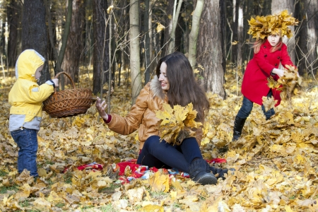Mother with two children sits on an edge of the autumn wood, collecting leaves  The girl in a red coat jealously looks at the brother Stock Photo