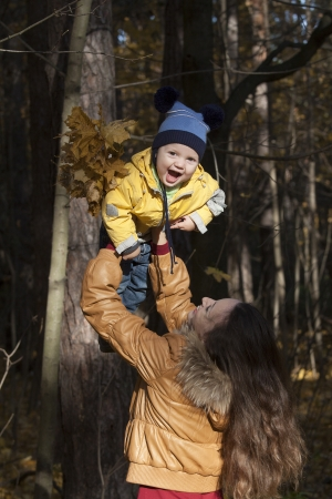 Mother plays with the laughing child, throwing up him up against the wood Stock Photo - 23221658