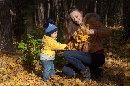 The boy in a yellow jacket helps mother to weave a wreath from leaves photo