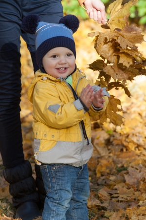 The boy in a yellow jacket claps against yellow leaves photo