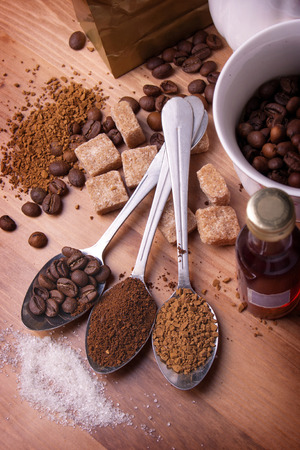 Teaspoons with various coffee lie on a table in an environment of sugar, cups and cognac