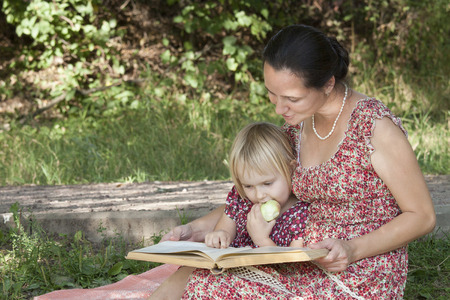 A blonde girl in a flowered dress gnaws apple, looking at a book that reads her mother Stock Photo