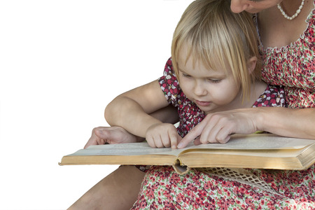 A blonde girl with mother reading a book lying on his mothers lap. White background.