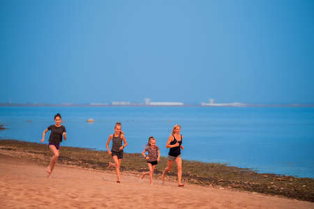 Children and adult girls run along the coast in sportswear on a background of nature at sunset