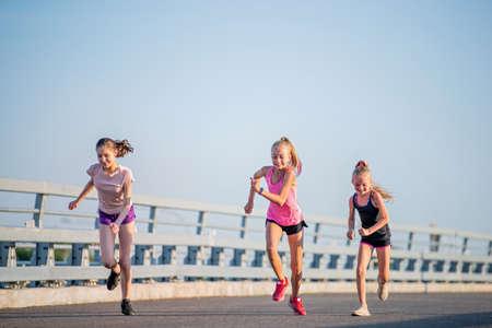 Three girls jogging on a sunny summer evening