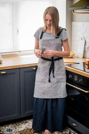 Happy woman in a linen apron stands in the kitchen and holds a dry bunch of lavender in her hands