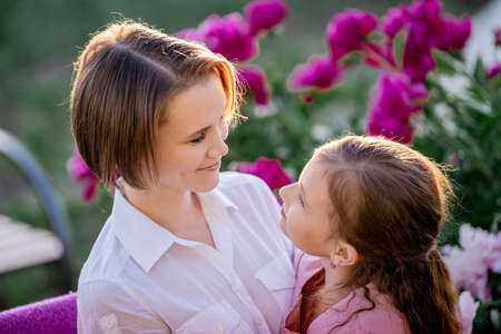 Happy family relationships. Mom and daughter sit on a bench and chat in the garden among the flowers on a sunny summer evening.