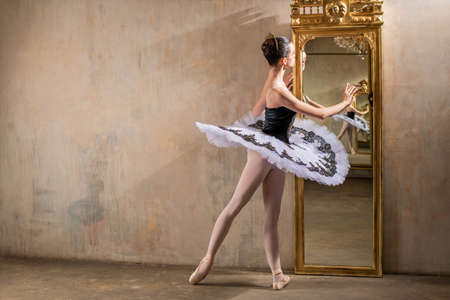 A young ballerina in a white tutu poses near a beautiful old mummer in a vintage interior, reflecting many times