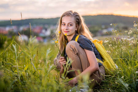 Portrait of a teenage girl with a backpack traveling on a summer evening against the backdrop of a landscape and sunset.
