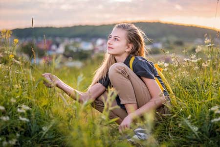 Portrait of a teenage girl with a backpack traveling on a summer evening against the backdrop of a landscape and sunset. Stock Photo