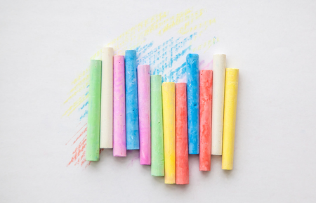 A colored multicolored chalk on a white background in vertical order, on which an abstract drawing is drawn with this chalk.