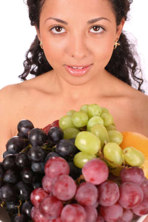 A smiling woman holds a plate with different sorts of grapes and other fruits, standing on white background. photo