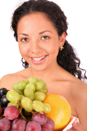 A smiling woman holds a plate with different kinds of fruits in her hands< standing on white background. photo