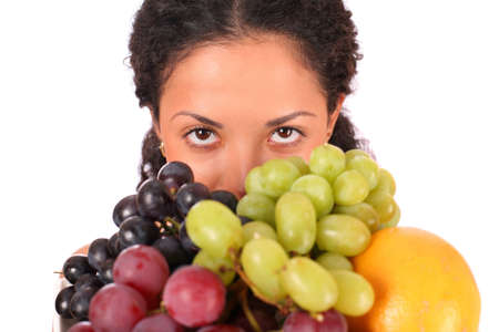 A woman holds a plate with different kinds of fruits in her hands, standing on white background. photo