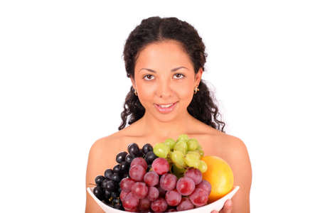 A smiling woman holds a plate with different kinds of fruits in her hands, standing on white background. photo