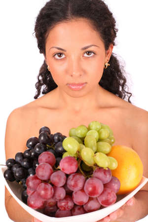 A sad woman holds a plate with different kinds of fruits in her hands, standing on white background. photo