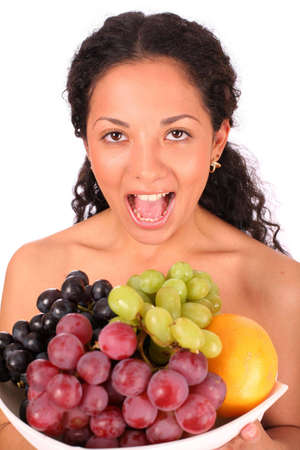 A crying woman holds a plate with different kinds of fruits in her hands, standing on white background. photo