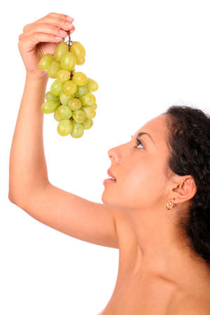 A woman looks on the bunch of grapes in her hands, standing on white background. photo