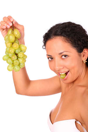 A smiling woman eats grapes and holds a bunch of grapes, standing on whire background photo