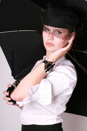 A young beautiful lady with a watch on her hand in a blak hat holding an umbrella standing over white background photo