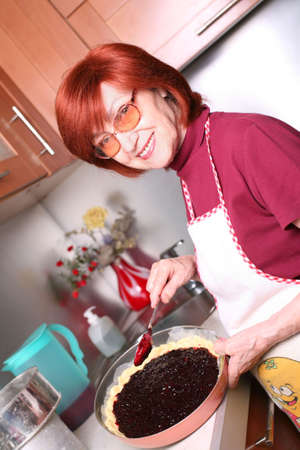 A smiling grandmother is cooking a jam tart Stock Photo