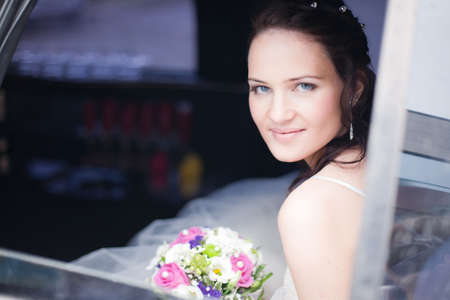 Attractive bride with a wedding bouquet sitting in the car
