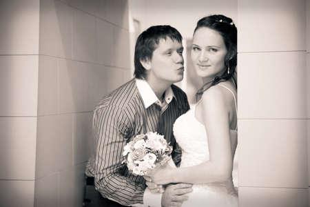 Handsome groom wants kiss his attractive bride photo