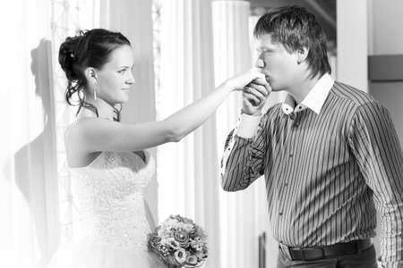 Groom kissing brides hand Stock Photo