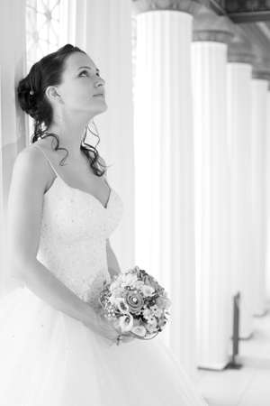 Attractive bride is holding a wedding bouquet and looking up Stock Photo
