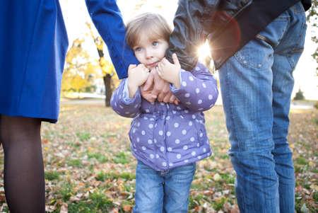 Sad little girl holds parents hands
